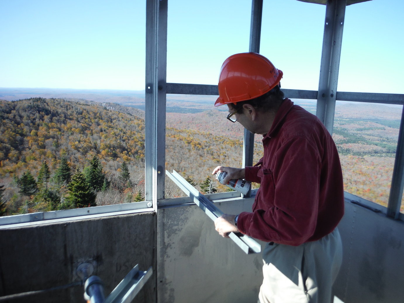 Bob spraying cold galvanization into drilled holes on window frame