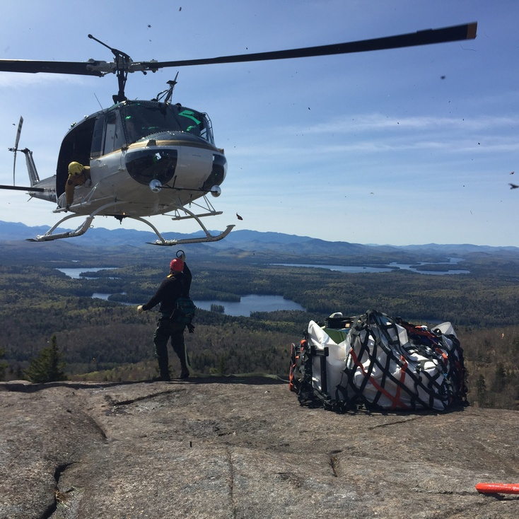 In this photo the NYS Forest Rangers are hooking a sling load of tools to be flown off the summit.
