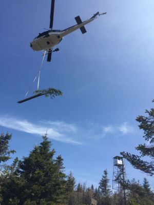 Here are the old braces being flown off the mountain. The tree tied to the back acts like a rudder – keeping the load from swaying back-and-forth. Note the new braces on the tower shining in the sun as the old braces are being flown off the summit.